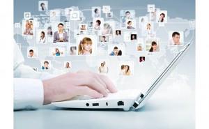 Мужские руки на клавиатуре современного белого ноутбука на фоне фотографий пользователей соцсетей, соединенных в виде схемы