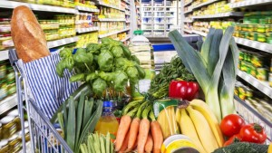 Detail eines Einkaufswagens mit Obst und Gem¸se zwischen Warenregalen im Supermarkt | Verwendung weltweit